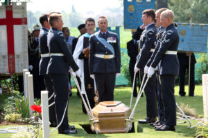 Members of the Queen's Colour Squadron lower the single coffin into the grave [Picture: Mike Drewett, Crown copyright]
